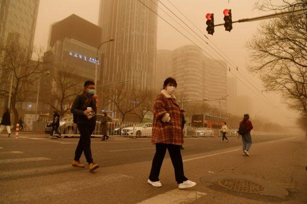 Przechodnie w Chinach podczas burzy piaskowej